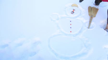 sněhulák : A girl in the snow drew a snowman and put a lid on his head
