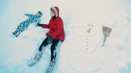 kardan adam : Mom and son playfully lying in the snow next to a snowman