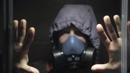 biyolojik : A man in a gas mask closed himself in a transparent room waiting for a chemical attack Stok Video