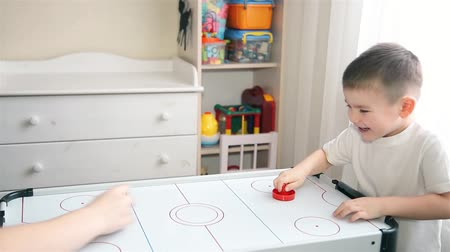 hokej : Mom and son play with passion in air hockey
