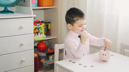 porquinho : The little boy counts the money in the piggy Bank