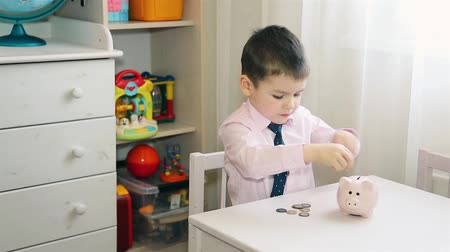 piggy bank : A little boy puts money in a piggy Bank