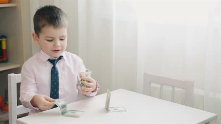 porquinho : Little boy folds paper money HD 1080p Stock Footage