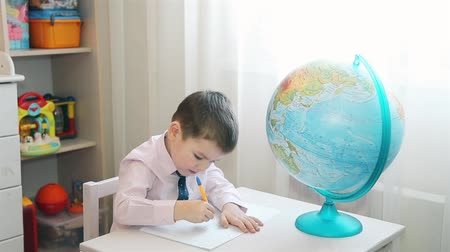 naturalist : Boy studying planet earth and writes notes in a notebook