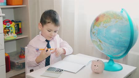 doesnt : A little boy counts his savings on a calculator and writes in a notebook
