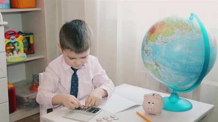 naturalist : A little boy counts his savings on a calculator and writes in a notebook HD