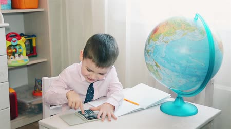 doesnt : Little boy counts his savings on a calculator Stock Footage