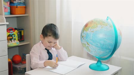 doesnt : The child studies the planet Earth and writes notes in a notebook Stock Footage