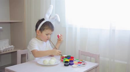 rabbit ears : A boy dressed as a hare paints an Easter egg