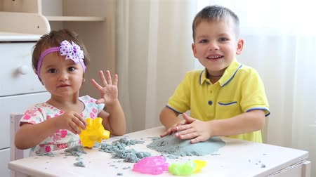 kinetik : Brother and sister play together with kinetic sand in childrens room at white table HD 1920x1080