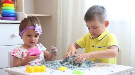 kalıp : Children in the nursery play together with kinetic sand gray HD Stok Video