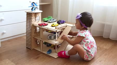 mateřská škola : Small child playing in kindergarten in toy garage with small cars and helicopter HD Dostupné videozáznamy