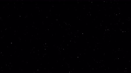 Slow motion of white particles in space in the form of small stars on a black background