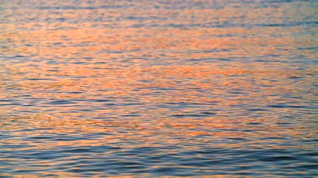 Beautiful sunset reflection on the calm sea surface, with natural wave motion.