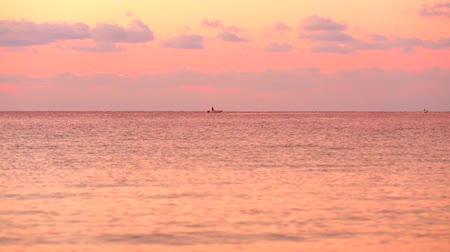 Beautiful cloudy sunset with beautiful pink reflection on the sea surface, with two small boat crossing the horizon Stock Footage
