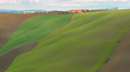 casas : Typical Tuscany landscape in crete Senesi, with farmhouse and cypress trees .. Clouds shadows moving fast in the field. Italy.