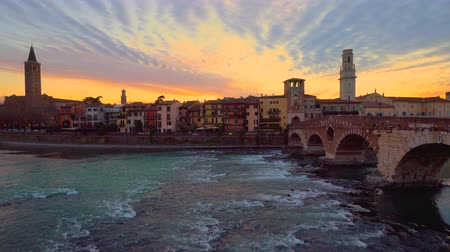 Sunset in Verona, Italy. View of old roman bridge Ponte di Pietra and Adige river flowing.