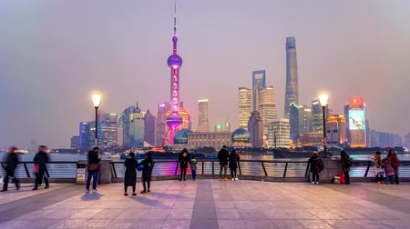 Timelapse of people walking on the Bund in front of Shanghai Skyline at sunset, China. Stock Footage