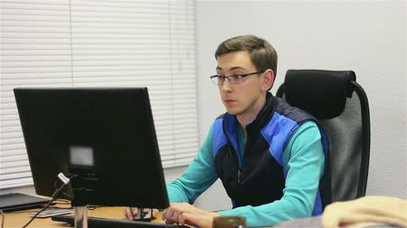 gry komputerowe : Young, handsome man sitting behind the desk and in using computer, then he is starting play game on pad. He is serious, neutral emotions