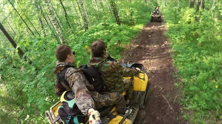 atv : Two guys on yellow quad ride through the forest Stock Footage
