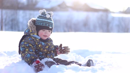 zimní : little boy in a winter cap playing in the snow Dostupné videozáznamy