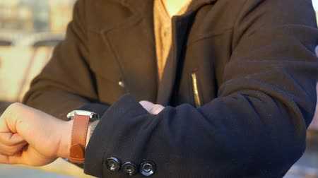 bilek : Man wearing wrist watches closeup shot on orage sun background Stok Video