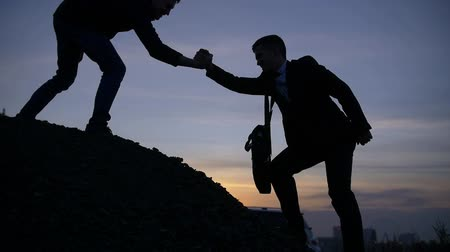 ajudar : Businessman silhouette gives hand to member to work together to the peak mountain