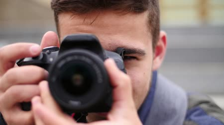 profi : Young handsome man takes photo of the camera with own camera and smiles Stock mozgókép