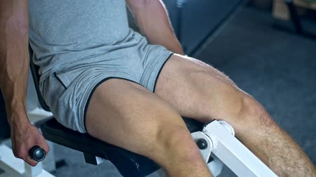 quads : Young athlitic man does leg extensions in gym