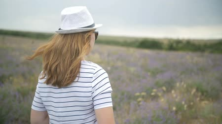 аромат : The girl in the hat is walking on a lavender field