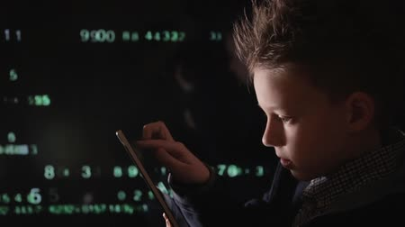 украсть : Young schoolboy prodigy - a hacker. Lots of digits on the computer screen.