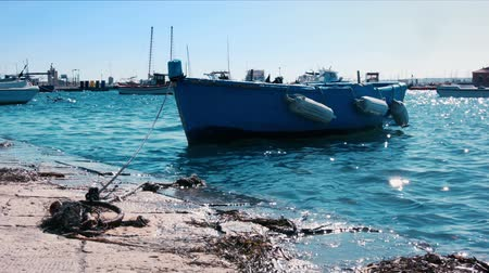 szicília : A small blue boat is rocked by the gentle waves of the turquoise mediterranean sea, bathing the docks of Marzamemi, a small fishing town in Sicily. Stock mozgókép