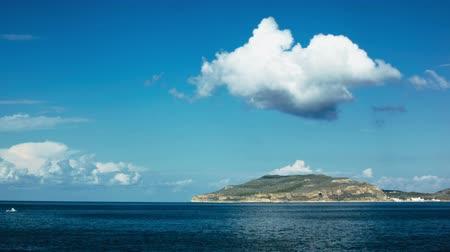 puffy clouds : Timelapse of blue sea and a big fluffy cloud over an island