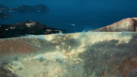 szicília : Wide shot panoramic time-lapse of Sicilian Egadi Volcano's island fumarole releasing white steam over a deep blue seaside mediterranean scenery Stock mozgókép