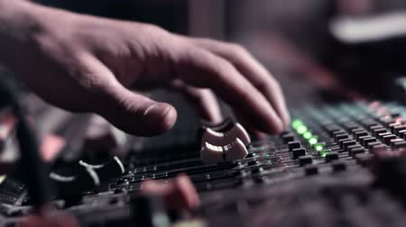 жить : Audio Engineer adjusting faders on his mixing console desk during a live event. Right pan, side view, very shallow DOF.