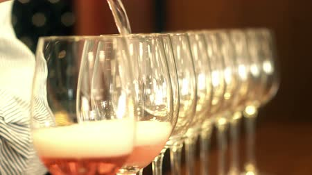 espumante : Sommelier hand pouring rose wine into a row of crystal glasses Vídeos