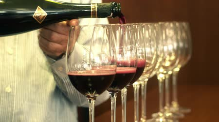 enchimento : Hand sommelier pouring red wine into a row of crystal glasses