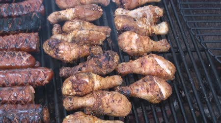 cozinhado : Chicken drumsticks on the fire pits grill 2. Sausages are incised to be better cooked inside and to allow smoke flavor penetrate more easily into the meat. Chicken drumsticks were marinated in salt and dry garlic.