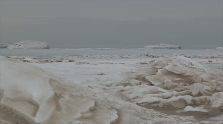 esquerda : Panning right to left of frozen Lake Michigan beach. Week of negative temperatures in Chicago. Three days after coldest day in 20 years. Stock Footage