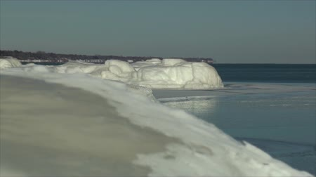 реальное время : Zoom out of Lake Michigan and frozen beach in Kenosha, Wisconsin.