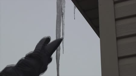 garagem : Breaking by hand icicle hanging from garages roof 2.