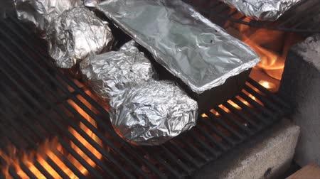 kamp ateşi : Cooking potatoes on the fire pits grill warped in aluminum foil. Stok Video