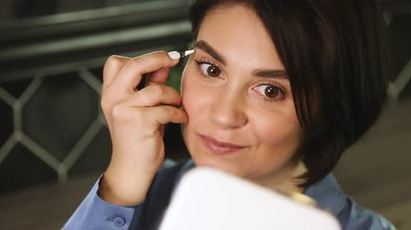 corrections : young European girl, brunette with short hair and white manicure, with brown eyes. plucking eyebrows with tweezers in front of a small mirror in a blue shirt for hours and smiling