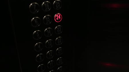odchodu : a mans hand presses the silver button on the floor in the elevator and it lights up red