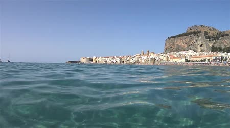szicília : Cefalù, Sicily. View of the city from the sea and the beach Stock mozgókép