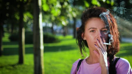 fumegante : A young Caucasian lady is smoking a cigarette on the street. Stock Footage