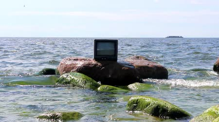 notion : Concept: ubiquitous TV. TV stands in waves, in background sailing ship. Birds fly
