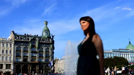 admires : Walk around city. Girl admires architectural beauty of St. Petersburg, Russia. In background is fountain, building in eclectic style and dome of Church