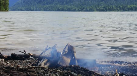 olhando a câmera : camp fire on  shore of mountain lake. Rest near water and  fire in  Altai