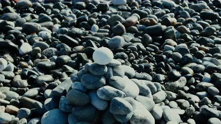 formado : Entertainment for beachgoers. Cairn, cone is formed of pebbles on seashore, with waves always